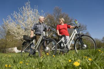Deutschland, Bayern, Senior Paar stehend mit Elektro-Fahrrad auf der Wiese